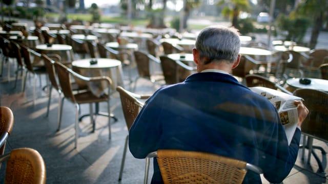 Ein Mann (von hinten) sitzt allein an einem Tisch draussen vor einem Café und liest Zeitung.