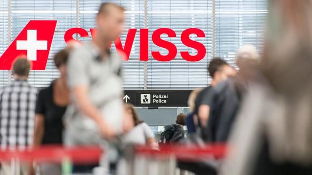 Passagiers a l'eroport a Turitg, en il fund il logo cotschen da la Swiss.