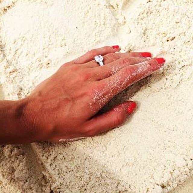 Eine Hand mit Verlobungsring in einem Herz aus Sand.
