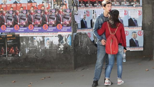 Junges Paar in Tiflis vor Wahlplakaten.