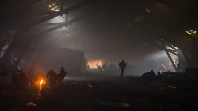 Eine verlassene Industriehalle im Rauch. An mehereren Stellen brennen Feuer, rundum sitzen jeweils ganze Menschengruppen und wärmen sich.