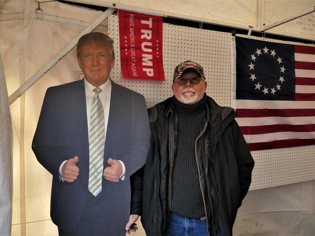 Eine Person steht neben einer Trump-Figur aus Pappe.