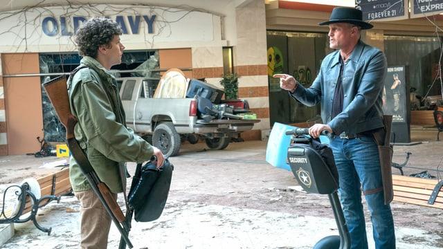 Zwei bewaffnete Männer auf Segways sind in einer verlassenen Shoppingmall.