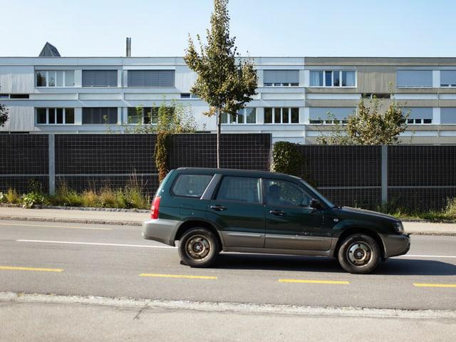 Auto fährt auf einer Strasse. Dahinter eine Wand. Im Hintergrund eine Häuserzeile.