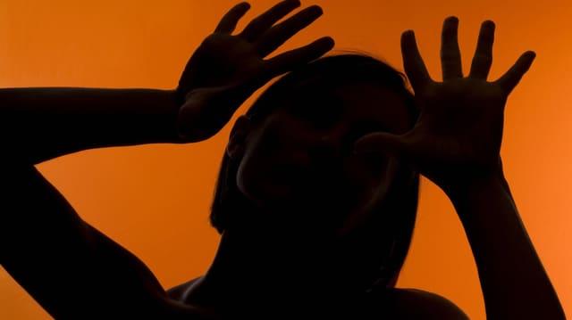 Silhouette einer gestikulierenden Frau vor farbigem Hintergrund.