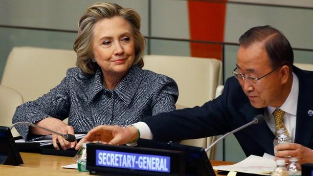 Die frühere US-Aussenministerin sitzt auf einem Podium neben dem UNO-Generalsekretär.