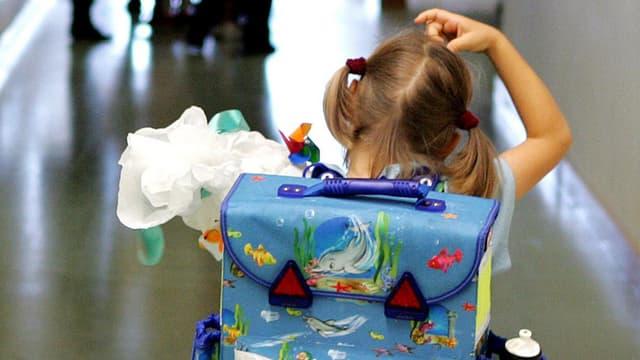 Mädchen mit Schulrucksack in einem Gang.