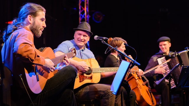 Vier Musiker mit Gitarren, Cello und Akkordeon auf einer Bühne.