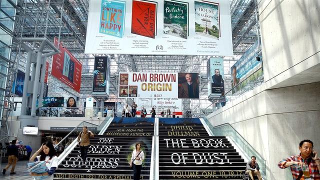 Grosse Halle mit Treppenaufgang. Überall hängen Plakate mit Büchern drauf.