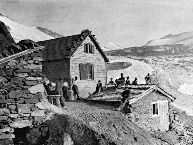 Männer um eine Berghütte postiert.