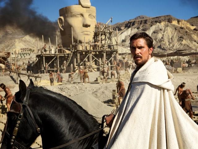 Schauspieler Christian Bale als Moses. Er sitzt in einem weissen Gewand auf dem Pferd.