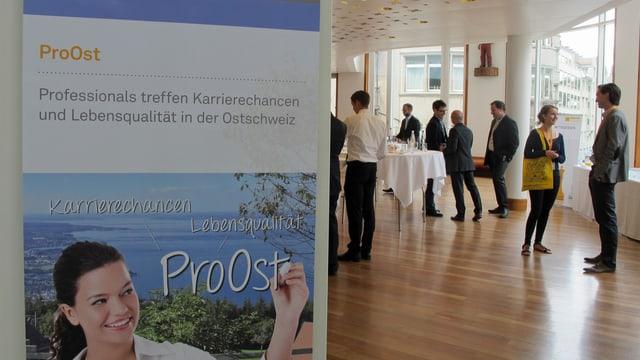 Plakat von der Jobvermittlungsmesse «ProOst» vor einem Raum mit Menschen