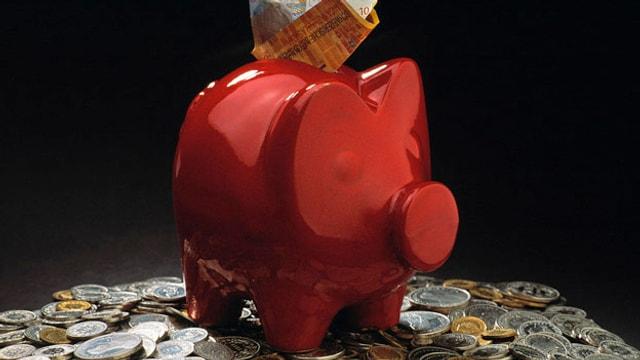 Ein rotes Sparschwein mit Münzen rundherum.