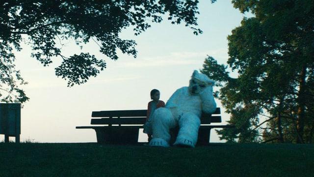 Kind mit riesigem überlebensgrossen Teddy auf Gartenbank sitzend.