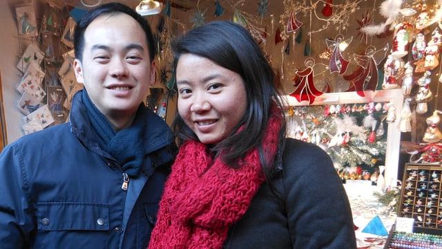 Japanisches Paar vor Stand an Weihnachtsmarkt.