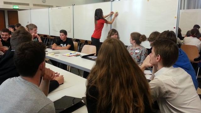 Schüler sitzen an einem Tisch, Frau klebt Zettel an Wandtafel.