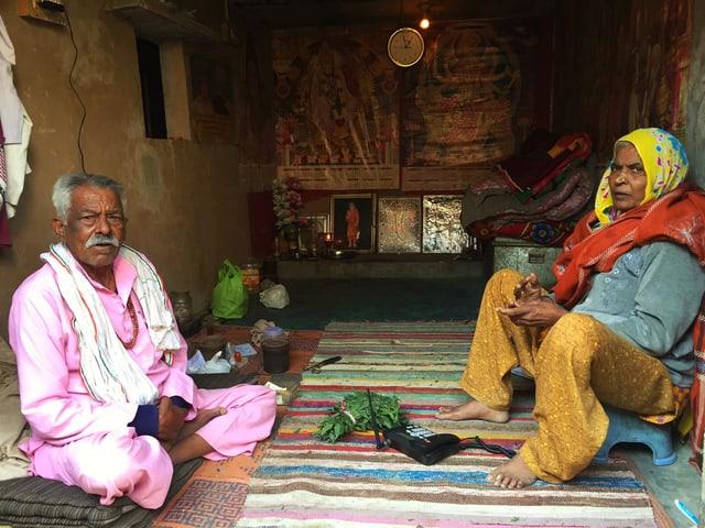 Ein älteres Paar sitzt auf dem Boden in seiner Hütte.