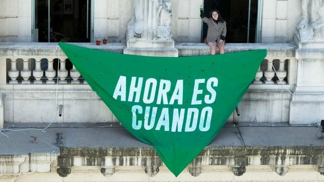 """Frau mit erhobener Faust sitzt auf einer Balustrade. Davor hängt ein grosses, grünes Dreicktuch mit der Aufschrift """"Ahora es cuando"""""""