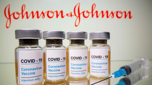Im Vordergrund Impfdosen von Johnson&Johnson und eine Impfspritze, im Hintergrund das Logo von Johnson&Johnson