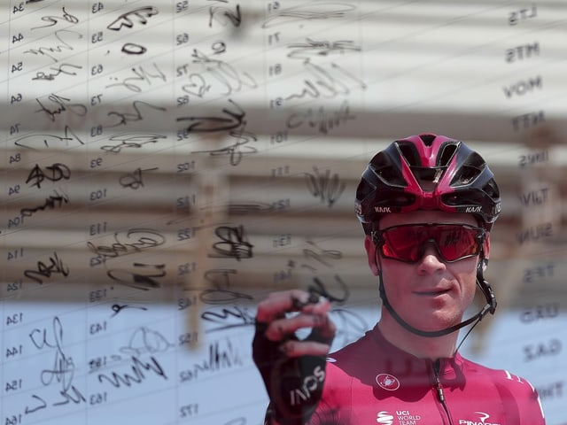 Chris Froome unterschreibt auf einer Plexiglas-Wand