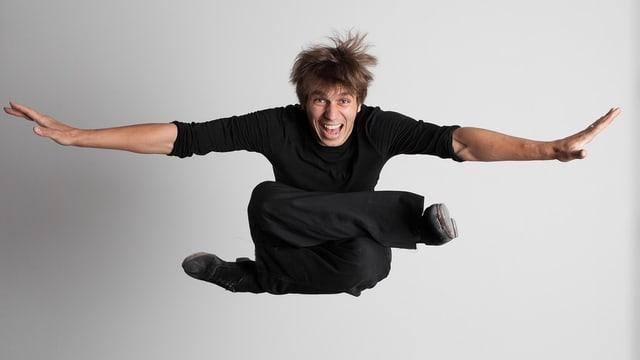 Ein Mann mit angezogenen Beinen springt.