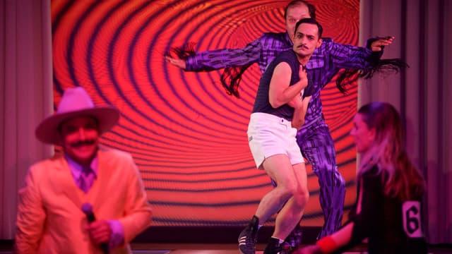 Eine Thetaerbühne: zwei Männer und eine Frau tanzen.
