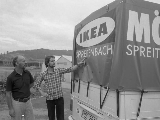 Zwei Ikea-Mitarbeiter stehen vor einem Transporter.