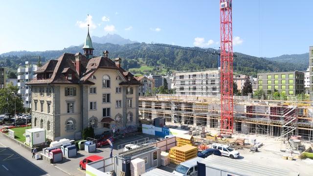 Ansicht einer Kleinstadt wo viel gebaut wird. In der Bildmitte Neubauten mit einem Baukran.
