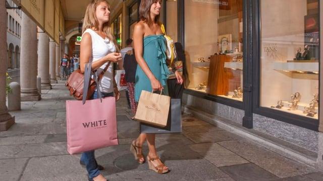 Zwei Frauen mit Einkaufstüten vor einem Schaufenster.