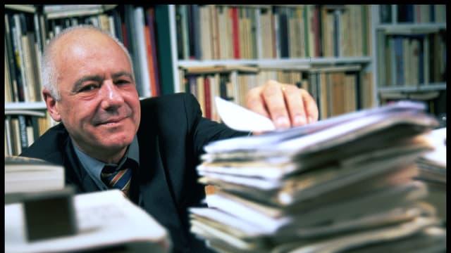 Jean-Christophe Ammann hinter einem Stapel Zeitschriften.