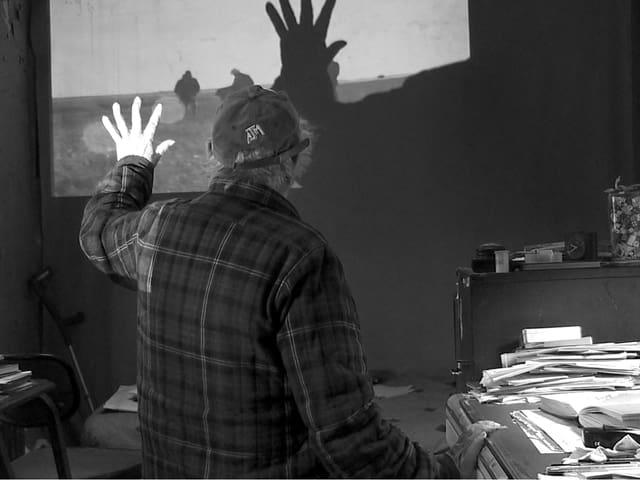 Ein Mann vor einem Film, der auf eine Wand projiziert wird.