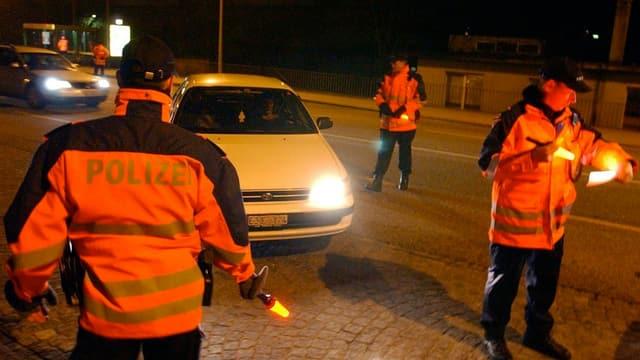 Ein Auto wird von Polizisten in Leuchtwesten angehalten.