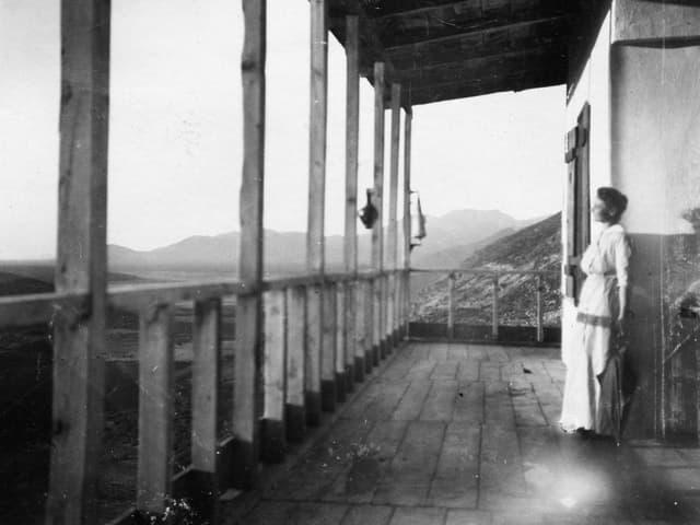 Altes foto einer Frau, die auf einer Veranda steht.