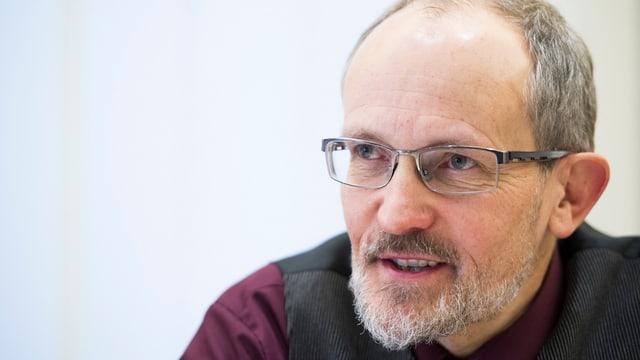 Ein Mann mit grauen Haaren, Bart und Brille.