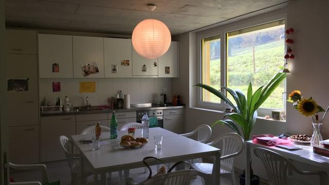 Die Küche des Allergikerhauses: Zwei Tische stehen im Raum, auf dem einen eine Sonnenblume, auf dem andere Getränkeflaschen.