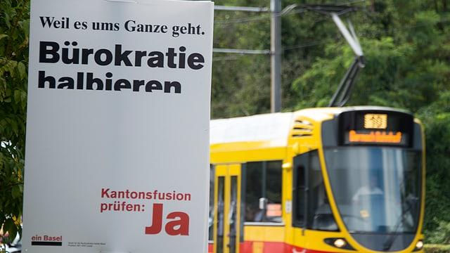 Auf einem weissen Plakat steht «Bürokratie halbieren. Kantonsfusion prüfen: Ja»