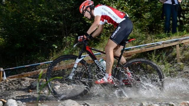 Reto Indergand fährt mit seinem Mountainbike durch einen Bach.