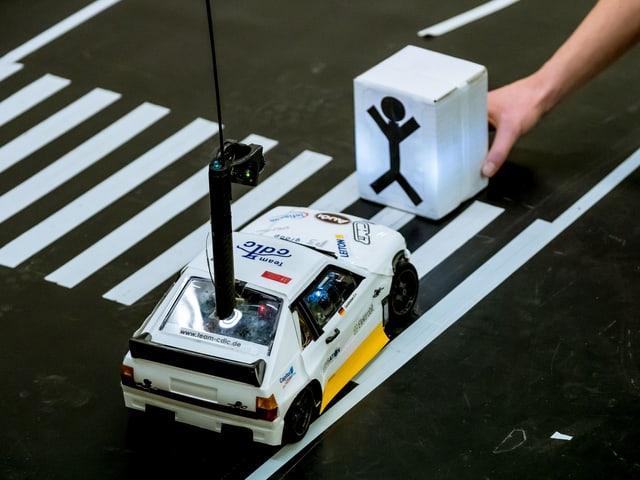 Modellauto hält vor einem Zebrastreifen