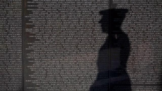 Ein Schatten vor einer Gedenktafel.