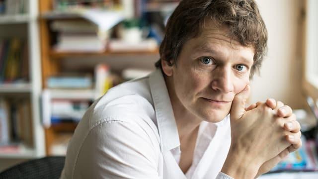 Christoph Simon stützt seinen Kopf mit seinen Händen. Er ist in einem Büro.