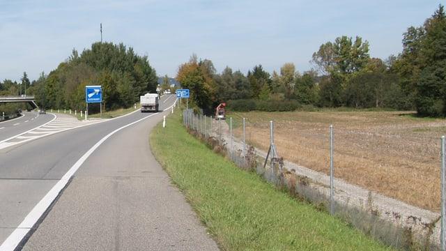 Ein Feldweg neben einer Autobahn-Auffahrt.