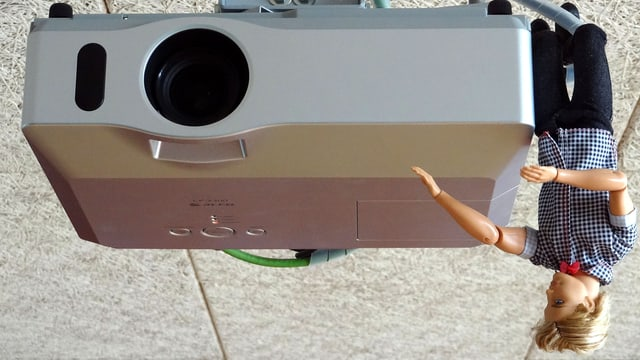 Ein Beamer/Projektor an der Decke, daneben Barbie-Ken.