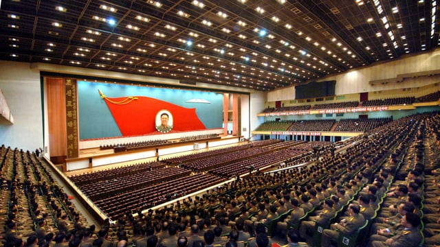 grosse Halle mit hunderten Militärs und Staatsdienern, im Hintergrund das Portrait von Kim Jong Il.