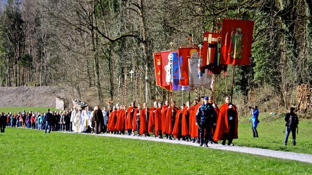 Die Fahnenträger sind mit roten Umhängen an der Prozession unterwegs.