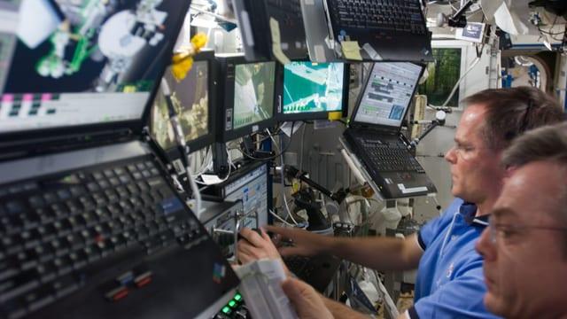Astronauten an Bord der ISS sitzen vor einer Reihe von an die Wand montierten Laptops.
