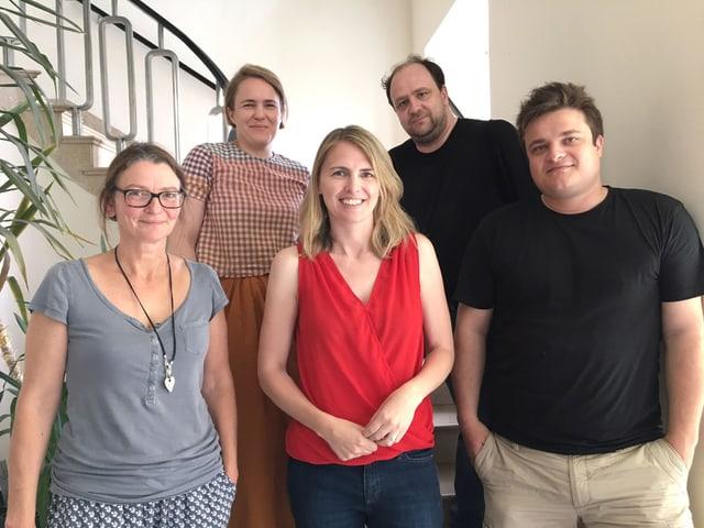 Fünf Redaktionsmitarbeiter stehen in einem Treppenhaus.