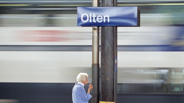 """Bahnhofs-Schilt """"Olten"""", im Hintergrund verschwommen ein Zug, der durchfährt, unten eine alte Frau, die auf dem Gleis steht."""