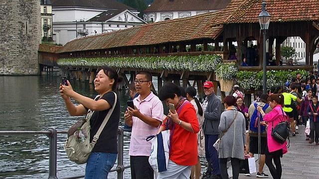 Asiatische Gäste fotografieren bei der Kapellbrücke in Luzern.