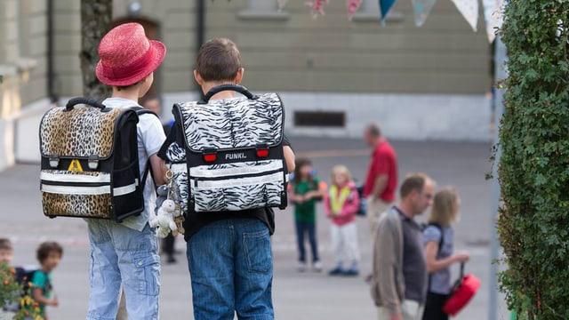 Zwei Schüler stehen am 1. Schultag mit ihren Ranzen vor dem Schulhaus