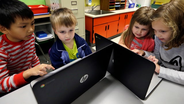 Kinder sitzen vor dem Laptop.